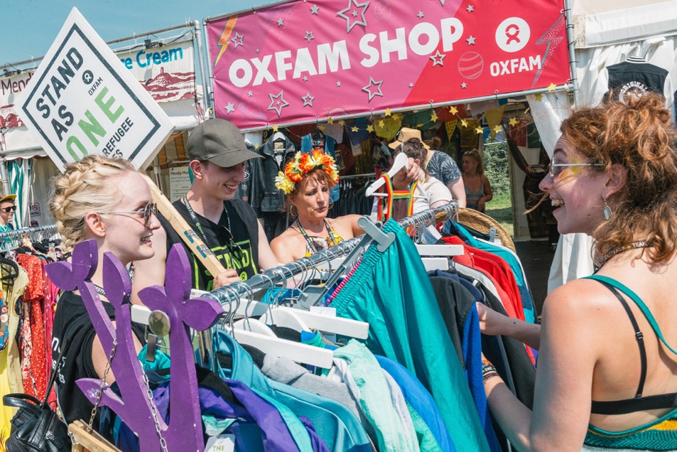 Festival goers having fun exploring the Oxfam treature trove (oxfam shop) at Glastonbury 2017.