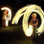 Two young lads juggle with fire at Stone Circle