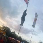Man climbs flag