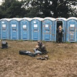 An excellent hippy having a psychedelic freakout with his guitar and amp in the mud by the toilets.
