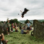 Young boy doing acrobatics off the stone circle